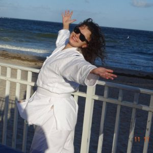 Cheerful Image of Julia in Her Martial Arts Uniform at the Beach With Open Arms and Big Smile