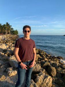 Image of Noah at the Beach Wearing Sunglasses.