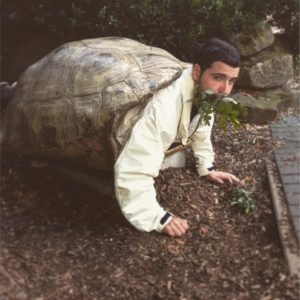 Image of Tomer Pretending to Eat Grass in a Giant Turtle's Shell.